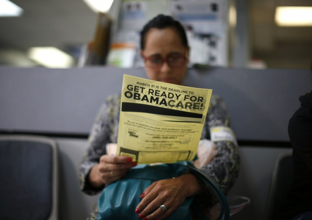 Murillo reads a leaflet at a health insurance enrollment event in Cudahy, California