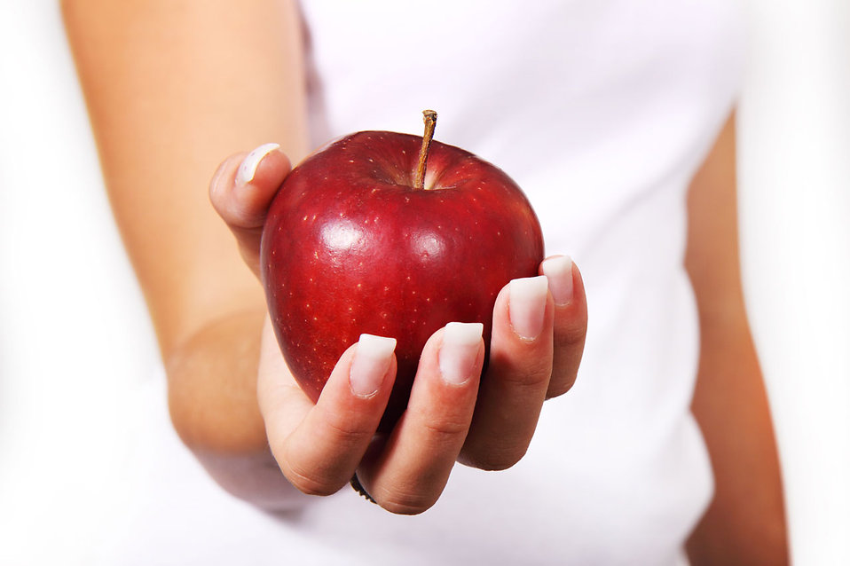 11712-close-up-of-a-woman-holding-a-red-apple-in-her-hand-pv